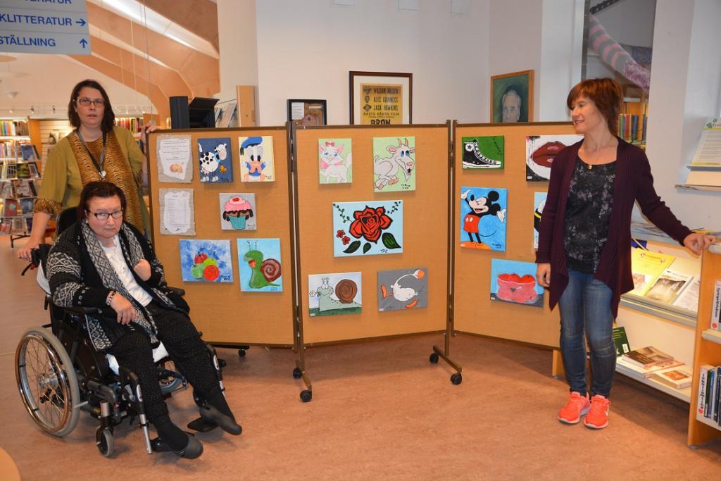 Ekelidens målargrupp ställer ut på biblioteket i Tyringe, från vänster konstnärerna Lotta Nilsson och Anette Öhman och Kristina Svensson i personalen. Foto: Berit Önell