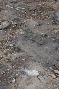 När det övre lagret järnvägsmakadam körts bort från ravinen har mer rödbrun makadam och asfaltbitar kommit i dagen.
