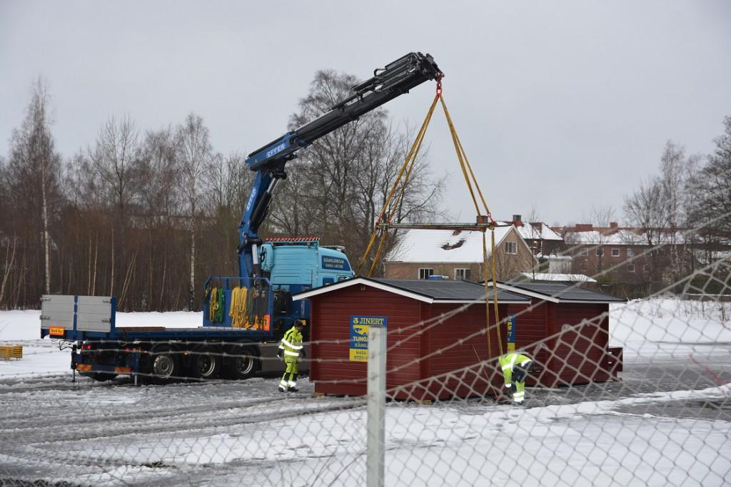 Några av de före detta valstugorna lyftes på tisdagseftermiddagen fram ur förrådsbyggnaden vid InMente för vidare transport till Stortorget inför julskyltningen. Bygglov är sökt för uppställning av fem stugor för EU-migranter i nöd på InMentes mark. Foto: Berit Önell