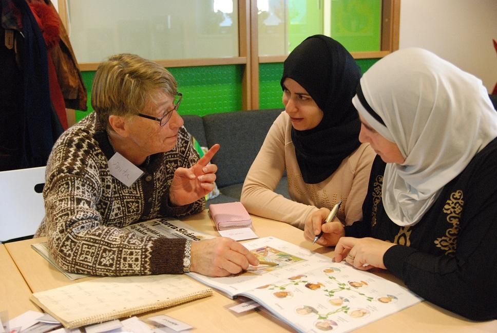 Anita lär Shalma från Palestina och Manal från Syrien att tala svenska på språkcaféet på Mötesplats Ljungdala.