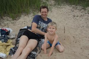 Jonas Rydström har doppat sig, trots algerna, men sonen David får bara bada fötterna.
