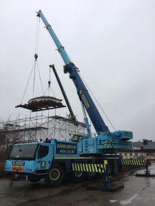 """Två stora kranar från Jinerts lyfte paviljongens tak på plats på det nya fundamentet inne i """"tältet""""."""