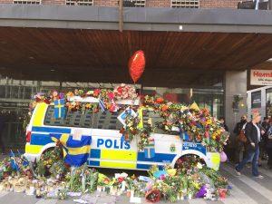En polisbuss är dekorerad med blommor utanför Åhlens City. Foto. Berit Önell