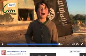 Pojken sjugner med IS-flaggan vajande i bakgrunden