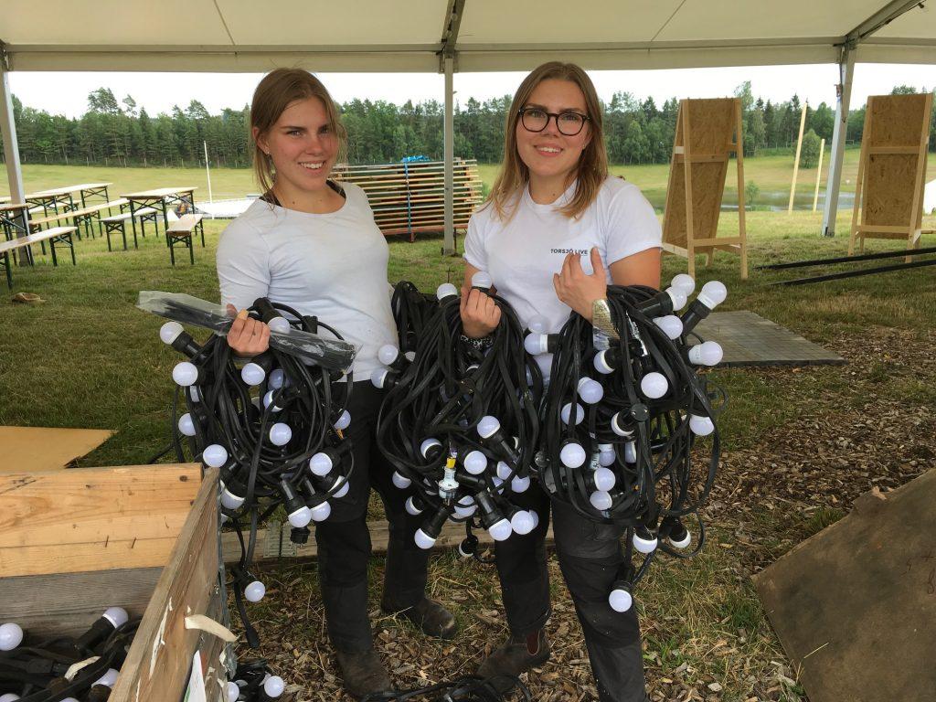Klara och Maja Johansson laddar på med lampor - på tur står att fixa så att entrén blir festligt upplyst.