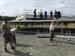 Tre starka killar turas om att påla ner förankringselementen till scenbygget. Christoffer Quick svingar slägghammaren, medan Daniel Karlsson och Alexander Lindström tar igen sig inför nästa pass.