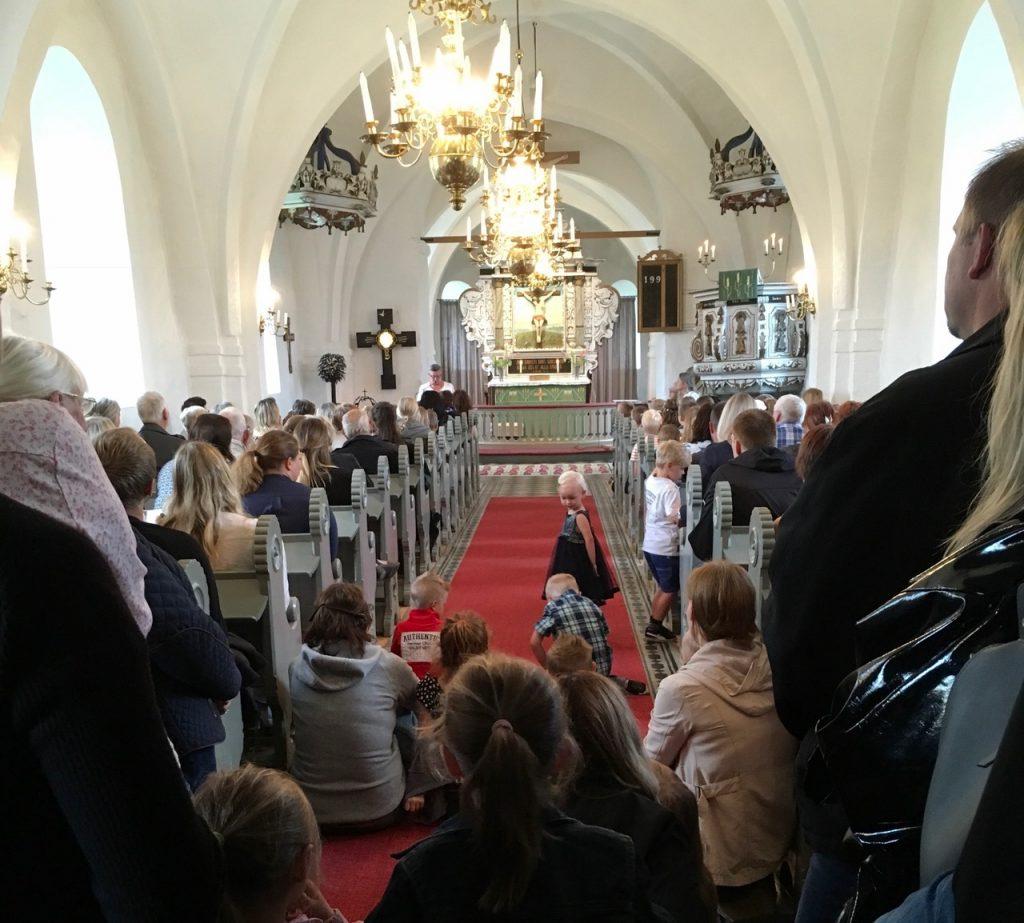 Det var helt fullsatt i Västra Torups lilla vackra kyrka. Drygt 160 personer får rum. Platsbristen är ett litet orosmoment, men än har man till allas glädje inte behövt vidta åtgärder för att begränsa deltagarantal för anhöriga. Connie Asterman, i talarstolen, hälsar alla välkomna.