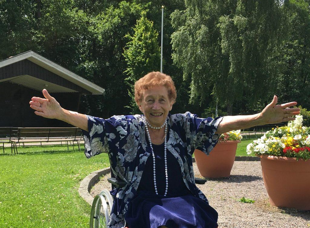 Elisabeth Wrambjer - lika glad och energisk som vanligt trots att hon för närvarande sitter i rullstol - hälsar alla välkomna till allsång i Åparken med start imorgon kväll.